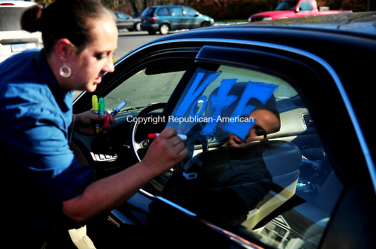 PLYMOUTH, CT, 08 NOV 11-110811AJ01- Nicole McWilliams of Terryville decorates her Honda in the parking lot of the Lyceum, a polling place in Terryville on Tuesday. McWilliams a Democrat, who is running for the library board, added plugs for Mayor Vincent Festa, herself and all local Democrats to the two side and rear window of her car.  Alec Johnson / Republican-American