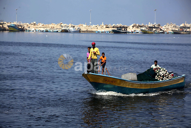 Palestinian fishermen work on their boats during a rally inside the port of Gaza to protest on the Israeli siege on the Gaza Strip and the five-year anniversary of the entry of first two ships solidarity with Gaza, in Gaza city, on Aug. 22, 2013. Photo by Ashraf Amra