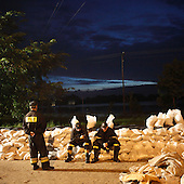 DOBRZYKOW, POLAND, MAY 24, 2010:.Rescue workers resting on  the sand bags wall, early morning..The latest chapter of disastrous floods in Poland has been opened yesterday, May 23, 2010, after Vistula river broke its banks and flooded over 25 villages causing evacualtion of most inhabitants..Photo by Piotr Malecki / Napo Images..DOBRZYKOW, POLSKA, 24/05/2010:.Strazacy wczesnym rankiem odpoczywaja na scianie z workow z piaskiem. Najnowszy akt straszliwych tegorocznych powodzi zostal rozpoczety wczoraj gdy Wisla przerwala waly na wysokosci wsi Swiniary kolo Plocka..Fot: Piotr Malecki / Napo Images ..