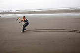 USA, Washington State, Long Beach Peninsula, International Kite Festival, Cameron Hendricks a young athletic boy flies a power kite that drags ends up dragging him along the sand