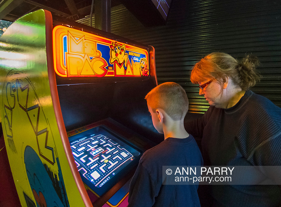 Garden City, New York, USA. December 12, 2015. A 6-year-old boy plays the classic 1982 Bally/Midway arcade game Ms. Pac-Man, as family member looks on, during Opening Day of Arcade Age exhibit, in an arcade set up at Cradle of Aviation Museum in Long Island. Admission includes unlimited free pay-to-play of video arcade games. Exhibit runs from Dec. 12, 2015 through April 3, 2016.