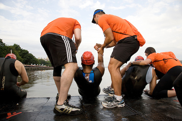 Minda's handlers Shawn and Rob lift her up to put her in the water at the start of the Aquaphor New York City Triathlon in New York on July 8, 2012.