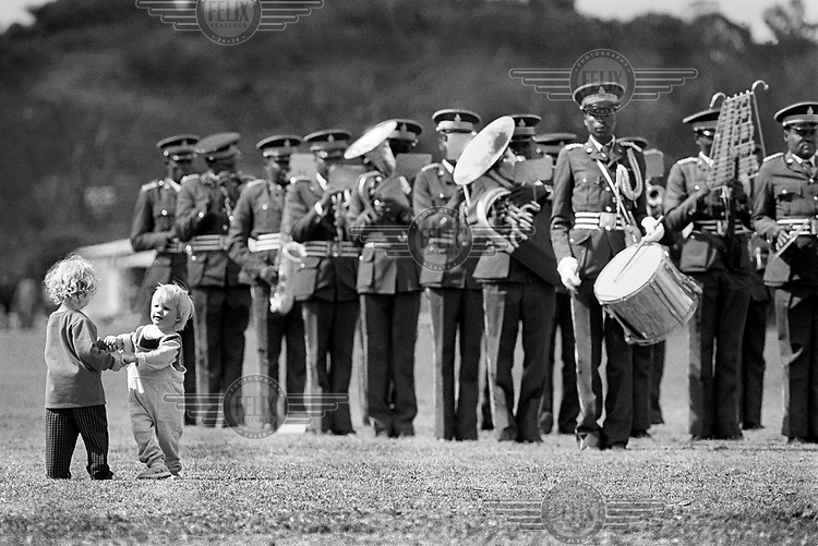 A military band plays while two white children dance in Harare.