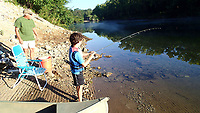 NWA Democrat-Gazette/FLIP PUTTHOFF <br /> Ivy Beasley, 8, catches a rainbow trout from the White River below Beaver Dam while fishing with his grandpa, Kenny Tessaro (left) of Tontitown.