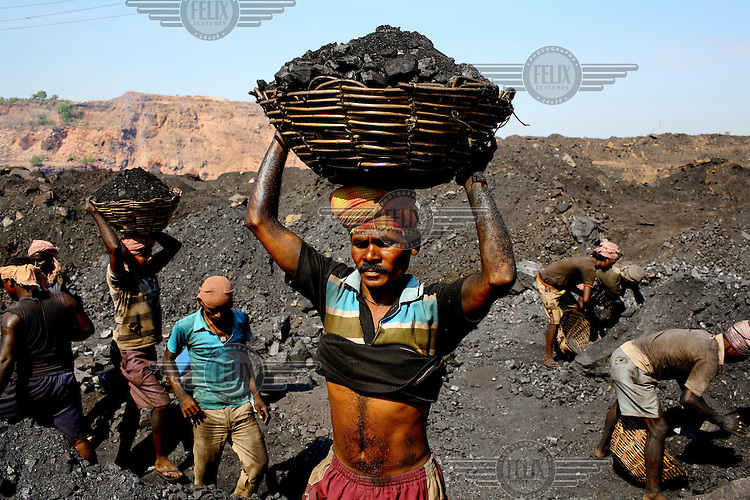 Contract labourer at an open cast coal mine carry baskets of rock coal to a waiting truck. After working for 10 - 12 hours per day they'll earn less than GBP 2.20. /Felix Features