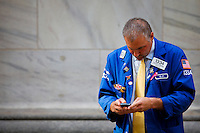 "A New York Stock Exchange ""NYSE"" trader checks his mobile phone during a break outside NYSE's building in New York. 15/10/2012. American International Group, Inc. (AIG) is a leading international insurance organization serving customers in more than 130 countries. Photo by Eduardo Munoz Alvarez / VIEWpress."
