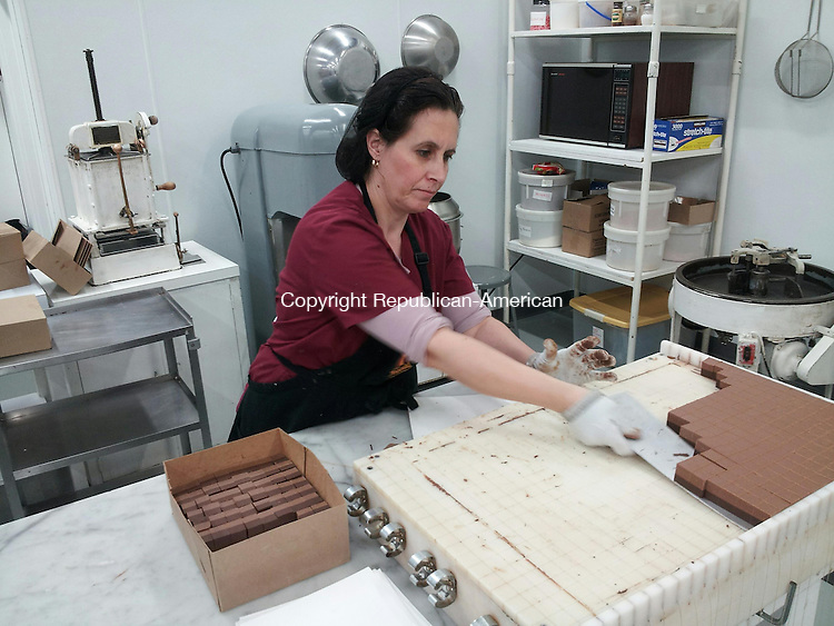 WATERBURY, CT- 11 February 2014- 021114BJ01-- Ilda Avxhiu of Fascia's Chocolate breaks away hazelnut truffles at the company's facility on Chase River Road. Company officials are cognizant of the food allergies and label their chocolates packaging. Bruno Matarazzo Jr. Republican-American