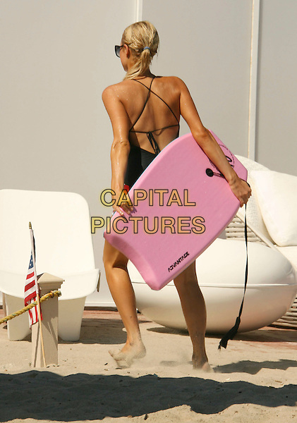 PARIS HILTON.Paris Hilton enjoys her Malibu Beach House and has some fun in the sun while boogie boarding in the Malibu surf, Malibu, California, USA..August 12th, 2007 .full length black top back behind rear pink boogie board wet.CAP/ADM/RE.©Russ Elliot/AdMedia/Capital Pictures
