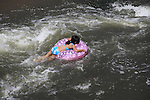 Girl floating in inner tube at Boulder Creek, Boulder, Colorado. .  John offers private photo tours in Denver, Boulder and throughout Colorado. Year-round.