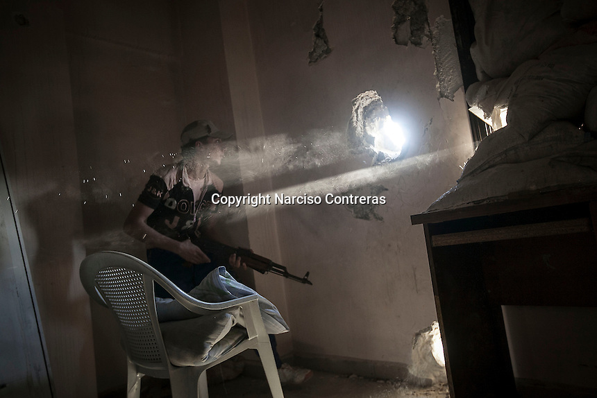 A rebel fighter retreats for cover after fires over his enemy's position as skirmishes spark out at the front line in Bustan Al Qasr frontline in Aleppo, Syria.