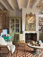 A grand 19th century gilt-framed mirror stands on an 18th century marble Provencal fire surround salvaged from a house in Arles