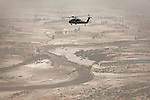 "A Blackhawk passes over Kandahar's Arghandab district. Scenes from the medical evacuations of wounded Americans, Canadians, and Afghan civilians and soldiers being flown by Charlie Co. 6th Battalion 101st Aviation Regiment of the 101st Airborne Division. Charlie Co. - which flies under the call-sign ""Shadow Dustoff"" - flies into rush the wounded to medical care out of bases scattered across Oruzgan, Kandahar, and Helmand Provinces in the Afghan south. These images were taken of missions flown out of Camp Dwyer in Helmand Province."