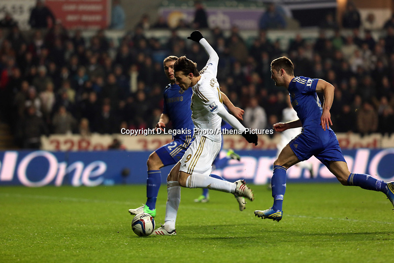 Wednesday 23 January 2013<br /> Pictured: Michu of Swansea (C) against Gary Cahill  (R) and Branislav Ivanovic (L) of Chelsea, takes a shot off target<br /> Re: Capital One Cup semi-final second leg, Swansea City FC v Chelsea at the Liberty Stadium, south Wales.