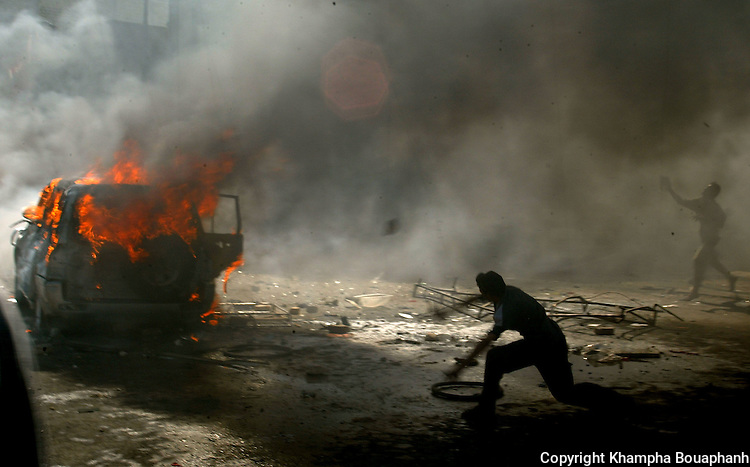 Iraqis  throw rocks at an SUV during a riot in central Baghdad on Monday, June 14, 2004.  (photo by Khampha Bouaphanh)