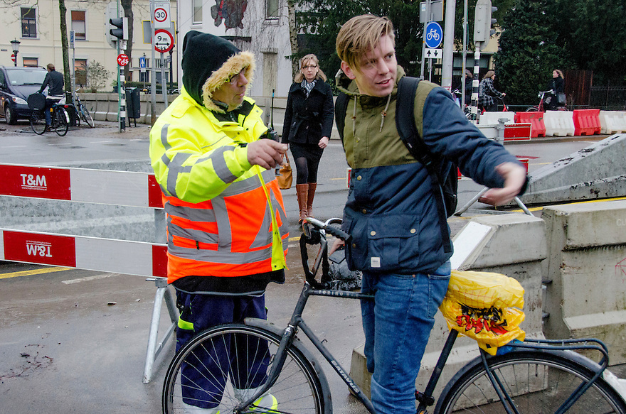 Nederland, Utrecht, 23 jan 2014<br /> Verkeersregelaar laat fietser afstappen op plek waar niet gefietst mag worden. Er ontstaat discussie.<br /> <br /> Foto: Michiel Wijnbergh
