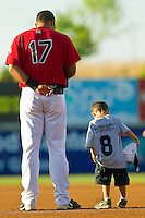 A young fan stands next to first baseman Jhonny Gomez #17 of the Hickory Crawdads during the National Anthem at L.P. Frans Stadium on April 29, 2011 in Hickory, North Carolina.   Photo by Brian Westerholt / Four Seam Images