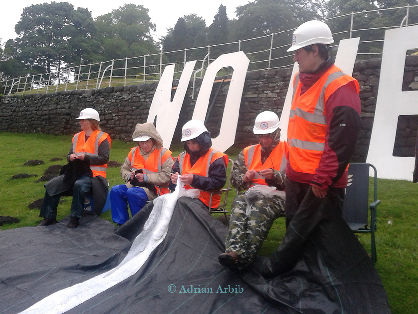 Knitting Grannies join <br /> 20 activists dressed in roadbuilders' high viz clothing and hard hats roll out a fake road in the field  immediately below Crag Hall, Cheshire in who's  grounds  the Chancellor  of the  exchequer George Osbornes has a residence .  <br /> The protest was made to highlight the expected  release of money for roadbuilding schemes throughout  the UK in the imminent spending  reivew on Wednesday 26th June