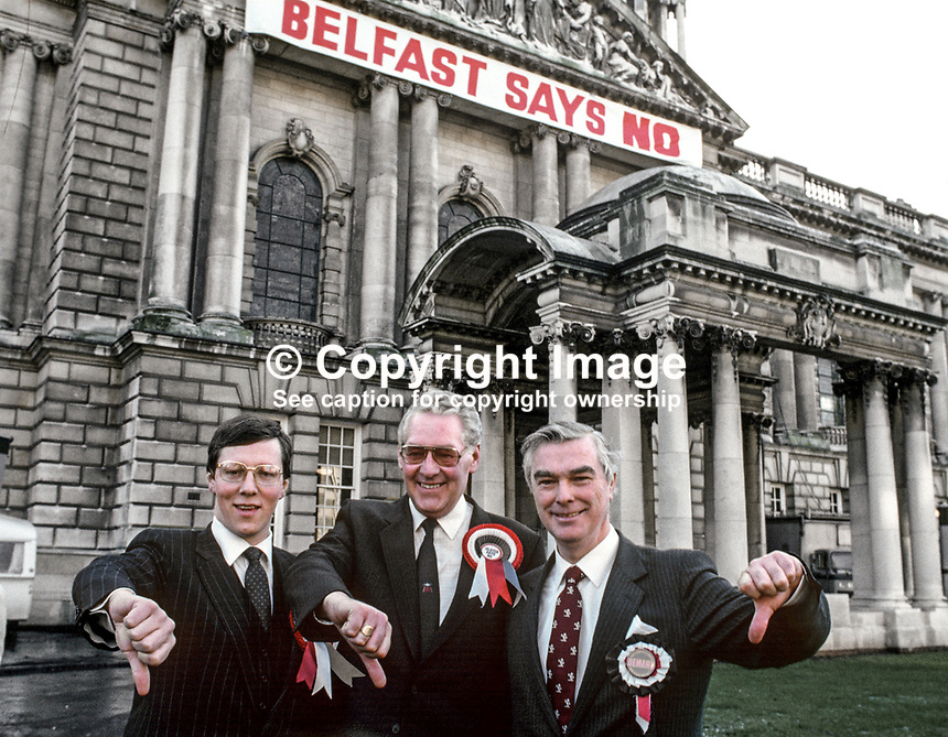Peter Robinson, Democratic Unionist, Cecil Walker and Rev Martin Smyth, both Ulster Unionist, give the thumbs down to the Anglo-Irish Agreement as they arrive at City Hall, Belfast, N Ireland, to lodge their by-election nomination papers. They were 3 of the 15 sitting unionist MPs  who resigned en masse in protest at the signing of the Anglo_Irish Agreement.  19860116AIA.<br />