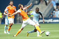 With an outstretched leg Adam Moffat (16) midfield Houston Dynamo  tries to take the ball off of Peterson Joseph..Sporting Kansas City and Houston Dynamo played to a 1-1 tie at Sporting Park, Kansas City, Kansas.