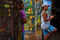 """Colombian sign painters hang out in the sign painting workshop in Cartagena, Colombia, 11 December 2017. Hidden in the dark, narrow alleys of Bazurto market, a group of dozen young men gathered around José Corredor (""""Runner""""), the master painter, produce every day hundreds of hand-painted posters. Although the vast majority of the production is designed for a cheap visual promotion of popular Champeta music parties, held every weekend around the city, Runner and his apprentices also create other graphic design artworks, based on brush lettering technique. Using simple brushes and bright paints, the artisanal workshop keeps the traditional sign painting art alive."""