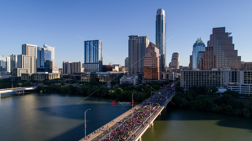 Aerial view from a drone as thousands of runners take start the race on the Congress Avenue Bridge during the Statesman Cap10K in downtown Austin, Texas