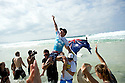 Taj Burrows (AUS) getting carried up the beach by his trainner and Mick Fanning after winning the Billabong Pipeline Masters on the Northshore of Oahu in Hawaii.