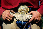 Working cowboy's clothing: leather chaps, blue jeans, western shirt and belt buckel. Cattle roundup at Santa Maria, California