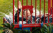 Washington, DC - June 25, 2009 -- White House Press Secretary Robert Gibbs falls into a water dunk tank as members of the news media threw balls at the target before a luau for members of Congress and their families on the South Lawn of the White House June 25, 2009 in Washington, DC. In a celebration of U.S. President Barak Obama's home state, the South Lawn was decorated with tiki torches and palm huts and the meal prepared by famous Hawaiian chef Alan Wong. .Credit: Chip Somodevilla - Pool via CNP