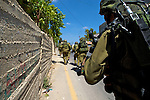 IDF soldiers move at speed to pursue stone throwing Palestinian youths into the West Bank village of Nabi Saleh near Ramallah on 02/07/2010.