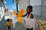 "A woman hangs laundry in a model resettlement village constructed by the Lutheran World Federation in Gressier, Haiti. The settlement houses 150 families who were left homeless by the 2010 earthquake, and represents an intentional effort to ""build back better,"" creating a sustainable and democratic community."