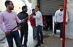 Men armed themselves with sticks after watching protesters flee tear gas during a demonstration against the interim government, in downtown Tunis, Tunisia, Jan. 17, 2011. The Tunisian police and army struggled to maintain order in the capital, as thousands of protesters once again filled the streets.