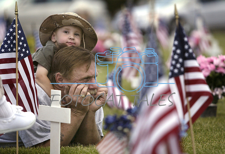 Mike Garrett and his son Mike Garrett Jr., 2, attended the Memorial Day ceremony at Lone Mountain Cemetary Monday afternoon, May 30, 2005, in Carson City, Nev. They sat with family members at the gravesite of Garrett's father, Army veteran Thomas Garrett..Photo by Cathleen Allison/Copyright Nevada Appeal