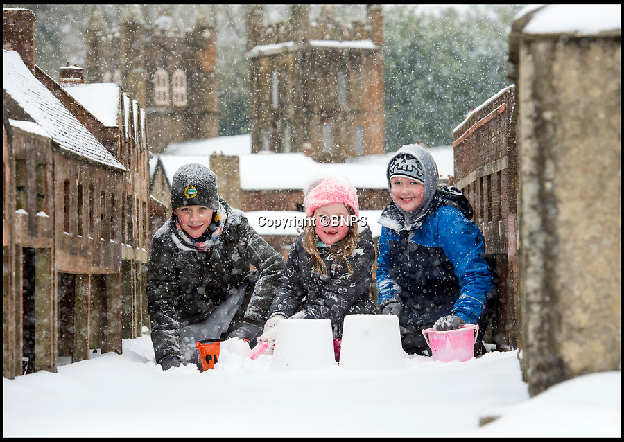 BNPS.co.uk (01202 558833)Pic: PhilYeomans/BNPS<br /> <br /> Schools Out - Rufus, Charlie and Florence Angus make the most of the snowfall in the lilliputian surroundings of Wimborne Model Town in Dorset.