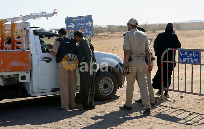 Egyptian policemen stand guard at the entrance of a road leading to Saint Samuel monastery in Minya province, some 260 kms south of the capital Cairo, on May 26, 2017. Masked gunmen attacked a bus carrying Coptic Christians on a visit to a monastery south of the Egyptian capital on Friday, killing at least 28 people including children, officials said. Photo by Amr Sayed