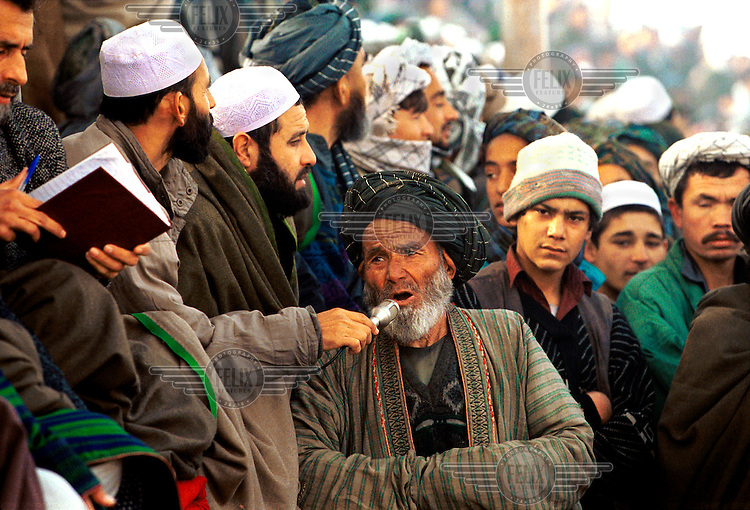 """© Tim Dirven / Panos Pictures..Mazar-e-Sharif, Afghanistan. December 2001...""""Ladeeeeez and Gennelmen..."""" An announcer grabs the microphone before a game of Buzkashi, Afghanistan's national sport. Literally translated as """"goat grabbing"""", it is played by two teams of men on horseback. They battle for control of a headless goat's carcass, with the objective of getting the carcass to a scoring circle. The game is said to date from the days of Genghis Khan, and remained popular despite being declared un-Islamic by the Taliban. To many Afghans, Buzkashi is not just a game, it is a way of life."""