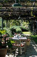 Freshly cut flowers on a table beneath a shady arbour that runs the length of the garden