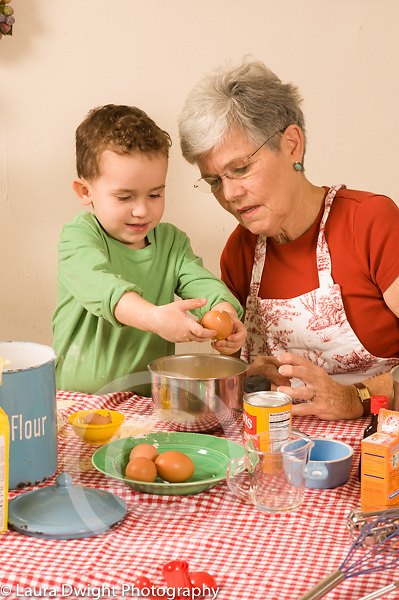 3 year old boy cooking baking activity with grandmother, cracking raw egg into bowl