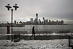 United States, New Jersey. A man walks by the side walk covered partially with snow while the skyline of Lower Manhattan and One World Trade Center are seen after the pass of the nor'easter winter storm from Exchange Place in New Jersey. 08/11/2012. Photo by Eduardo Munoz Alvarez / VIEWpress.