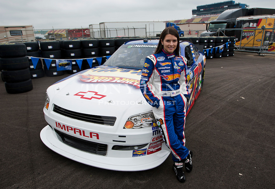 Danica Patrick poses for pictures with her new Hot Wheels NASCAR racecar, featuring its iconic red and orange flames, Thursday, Aug. 12, 2010, at Michigan International Speedway in Brooklyn, Mich. Hot Wheels debutes its sponsored racecar, in a new format for the NASCAR Nationwide Series, at this weekend's CARFAX 250 Nationwide race. (Tony Ding/ APImages forMattel, Inc.)