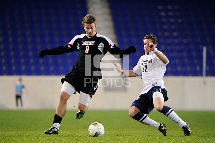 Max Wasserman (22) of the Connecticut Huskies goes for the tackle on Colin Rolfe (9) of the Louisville Cardinals. Connecticut defeated Louisville 1-0 during the first semifinal match of the Big East Men's Soccer Championships at Red Bull Arena in Harrison, NJ, on November 11, 2011.