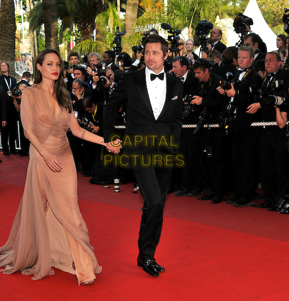 "BRAD PITT & ANGELINA JOLIE.The ""Inglourious Basterds"" Premiere at the Grand Theatre Lumiere during the 62nd Annual Cannes Film Festival, Cannes, France..May 20th, 2009.full length black tuxedo suit cream beige brown pink dress sheer long one shoulder tattoos couple holding hands slit split low cut neckline wrap.CAP/PL.©Phil Loftus/Capital Pictures."