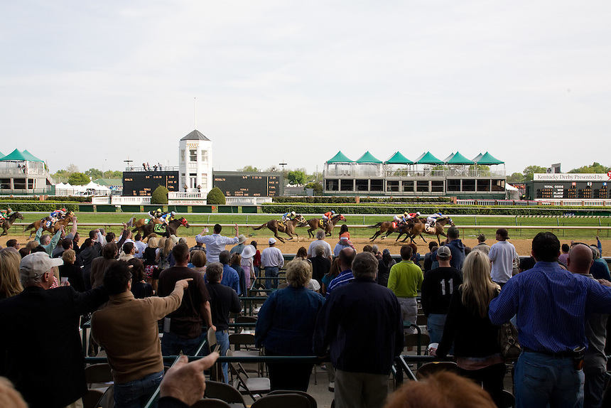 Horse race fans watch the finish of a race during Derby Week at Churchill Downs in Louisville, Kentucky.