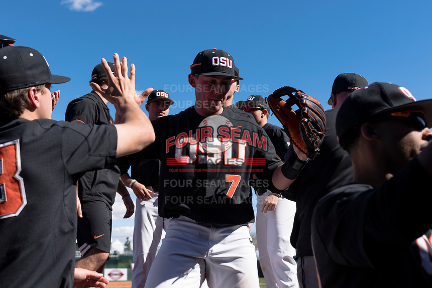 Oregon State Beavers right fielder Tyler Malone (7) is high-fived by teammates between innings of a game against the Gonzaga Bulldogs on February 16, 2019 at Surprise Stadium in Surprise, Arizona. Oregon State defeated Gonzaga 9-3. (Zachary Lucy/Four Seam Images)