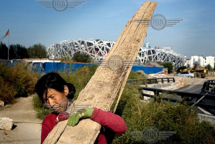 """A scavenger in Beijing collects wood from the construction site of the """"Bird's Nest"""" National Stadium, which will be unveiled for the 2008 Olympic Games"""