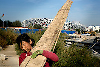 "A scavenger in Beijing collects wood from the construction site of the ""Bird's Nest"" National Stadium, which will be unveiled for the 2008 Olympic Games"