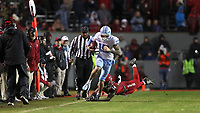 RALEIGH, NC - NOVEMBER 30: Beau Corrales #15 of the University of North Carolina breaks an attempted tackle by De'Von Graves #14 of North Carolina State University during a game between North Carolina and North Carolina State at Carter-Finley Stadium on November 30, 2019 in Raleigh, North Carolina.