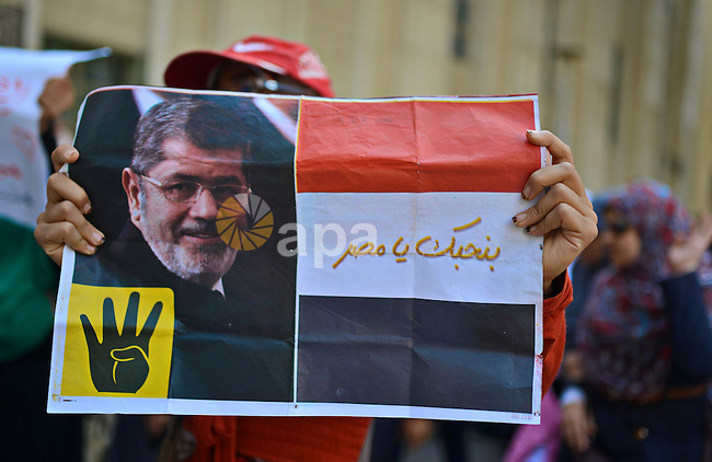 An Egyptian student who support Muslim Brotherhood hold a picture of ousted President Mohammed Morsi, during a demonstration demanding for release her fellow Radwa Jamal, who was arrested by Egyptian police, at Cairo University on November 5, 2014. Photo by Amr Sayed