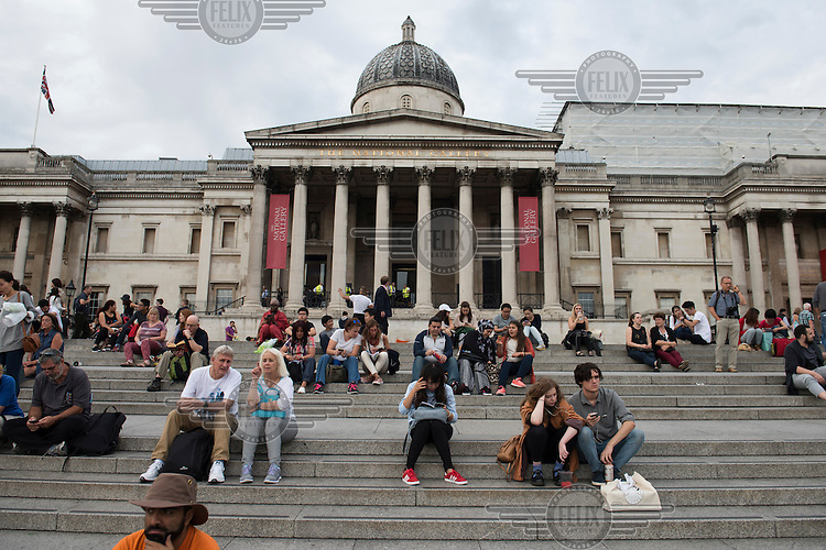 Tourists on the steps on the north side of Trafalgar Square with the facade of the National Gallery behind them.