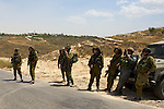 IDF soldiers laugh as small children unsuccessfully try to stone them as they man a road block between the Israeli settlement of Neve Tsuf & the Palestinian the village of An Nabi Salih near Ramallah on 11/06/2010. The road block was put in place due to a demonstration by the Palestinian residents of An Nabi Salih against the planned demolition of village houses by the Israeli military & remained in place following the demonstration.