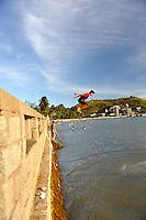 Boy jumping off sea wall at Bai Truoc (Front Beach), with Small Mountain (Nui Nho) in background. Hang Dua Bay, Vung Tau, Vietnam